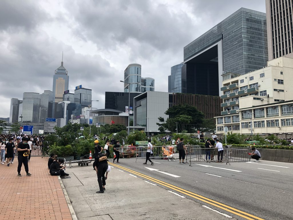 Makeshift barricades in front of the Legislative council and Chinese Army Headquarters (on the left). Protestors use metal barricades, trash bins and tree branches to enforce their positions.