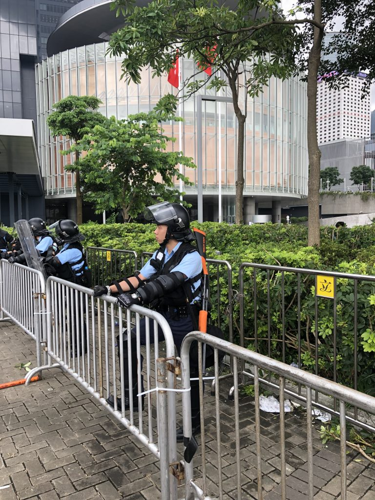 "Policeman carrying a ""less lethal"" weapon is guarding in front of the Legislative Council."